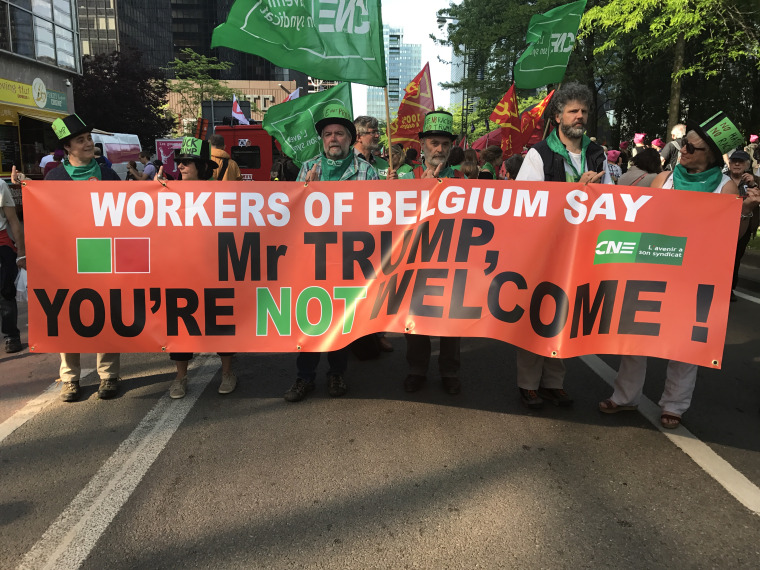 Belgian trade unionists hold up an anti-Trump banner during a protest against Donald Trump's visit on Wednesday.