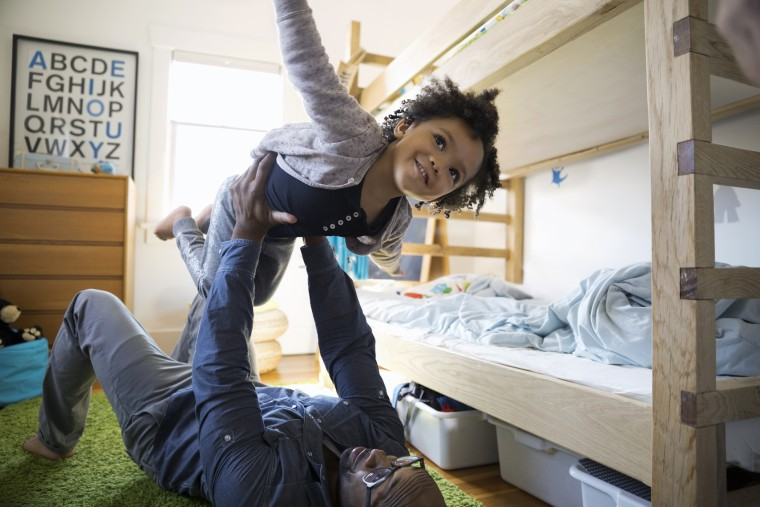 Image: Father Lifting Daughter in Bedroom