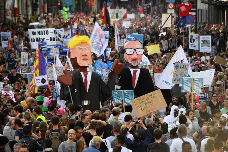 Image: People carry effigies of US President Donald Trump and Belgian Prime Minister Charles Michel during a demonstration
