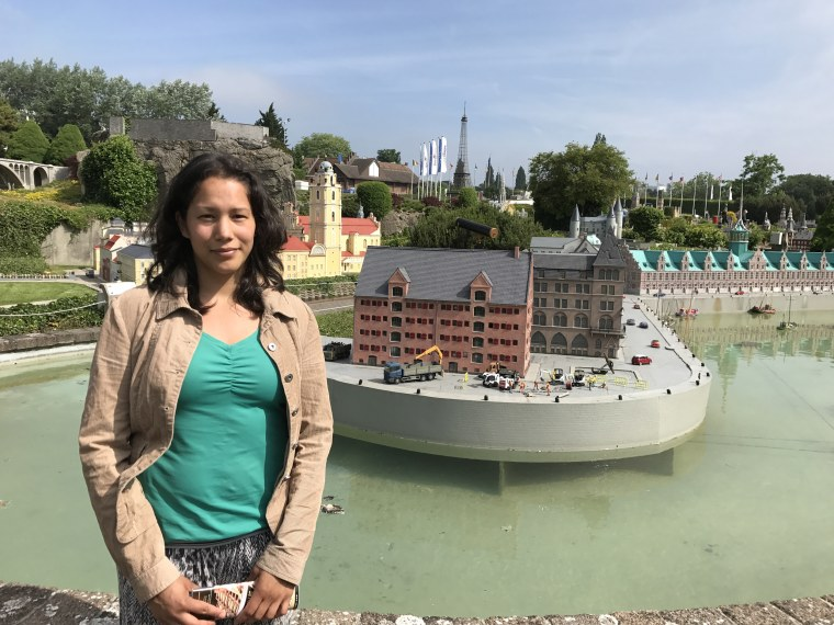 Image: Kerstin Maas-Enriquez poses in front of a miniature version of the Copenhagen stock exchange in Mini-Europe amusement park