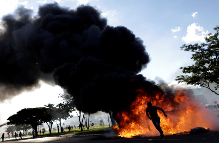 Image: A demonstrator runs near a burning barricade in Brasilia