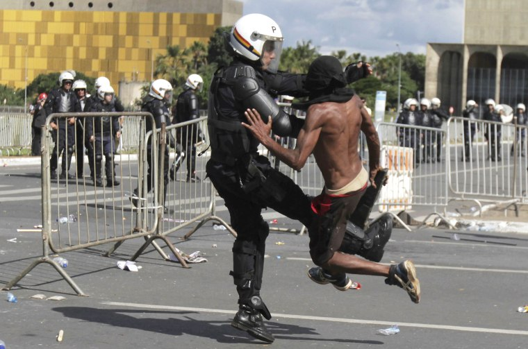 Image: A demonstrator clashes with a police officer during an anti-government protest in Brasilia