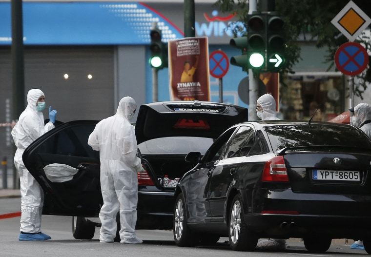 Image: Forensics officers inspect the car of former Greek prime minister and former central bank chief Lucas Papademos following the detonation of an envelope injuring him and his driver, in Athens