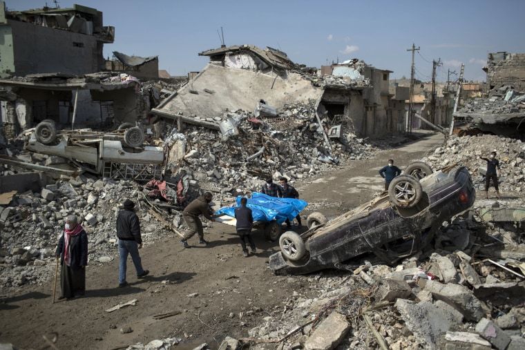 Image: Residents carry the bodies of several people killed during fighting between Iraq security forces and Islamic State militants on the western side of Mosul