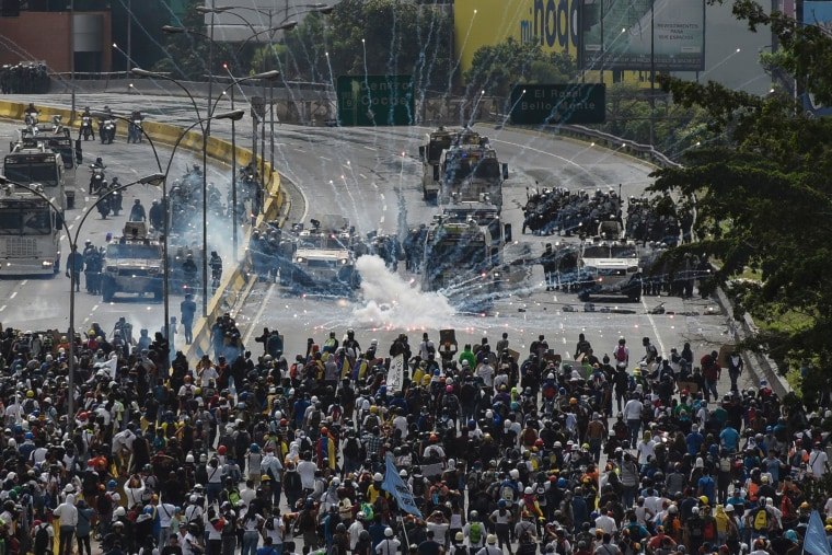 Image: Riot police clash with opposition demonstrators during a protest in Caracas