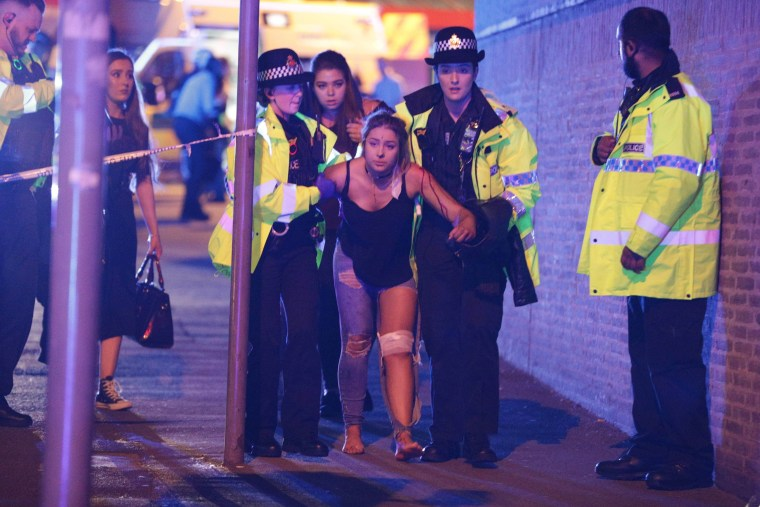 Image: An injured fan is helped by police and emergency personnel at the Manchester Arena after an explosion
