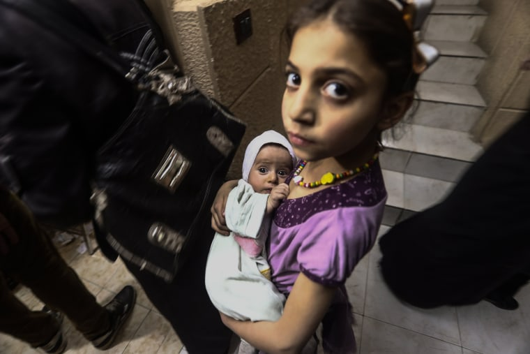 Image: A little girl holding her newborn sister waits for their turn for vaccinations