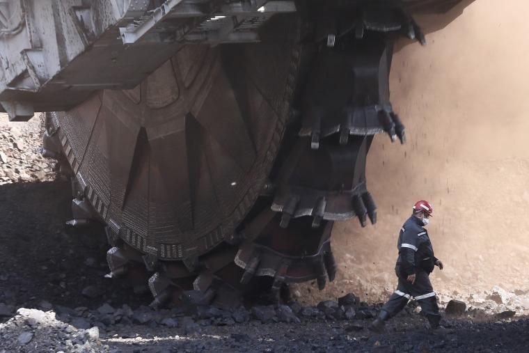 Image: An employee walks past a Soviet-made rotary dredge