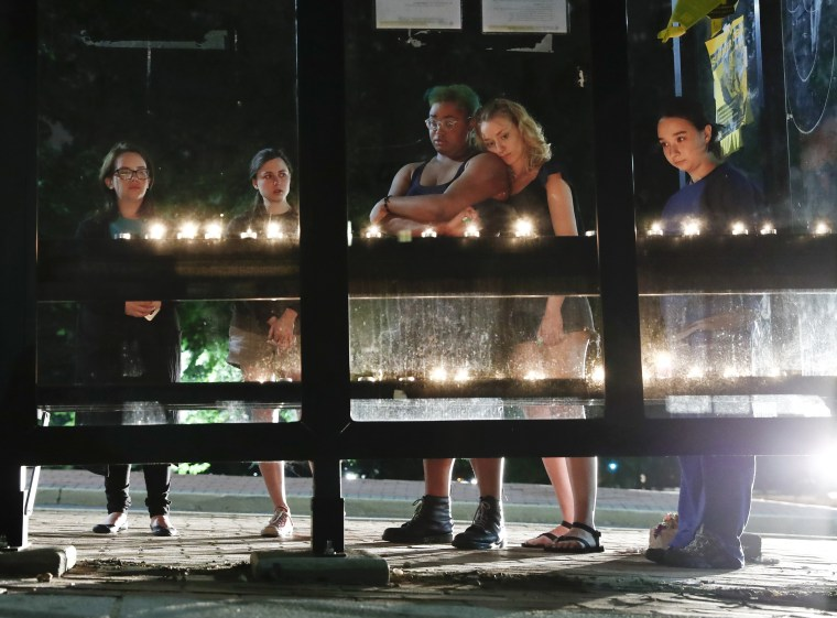 Image: People gather for a candlelight vigil at a bus shelter