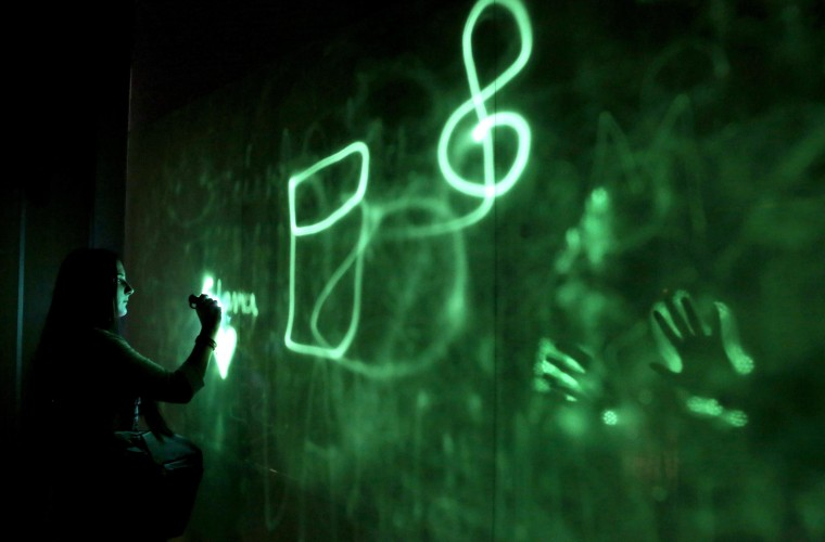 Image: A visitor uses a UV flashlight to paint on an installation
