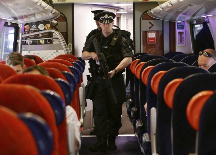 Image: Armed police patrol a train