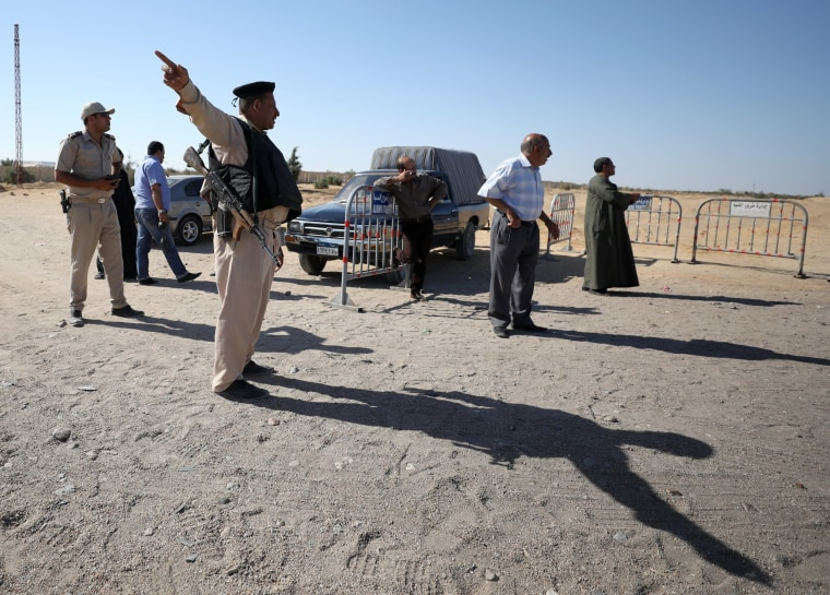 Image: A security guard gestures near the site of an attack that killed at least 26 people in Minya