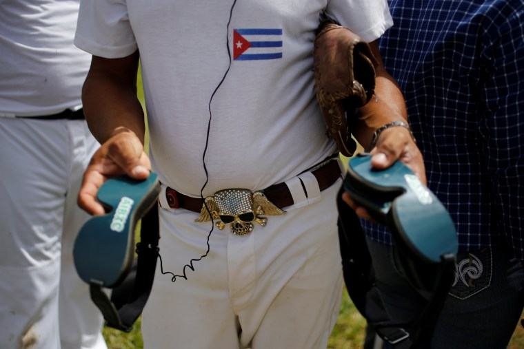 Image: Filiberto Socarras, who is visually impaired, holds googles during a baseball lesson at the Changa Medero stadium, in Havana