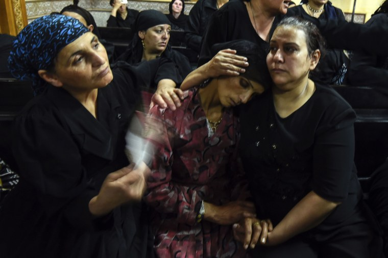 Image: Relatives of killed Coptic Christians grieve during the funeral at Abu Garnous Cathedral