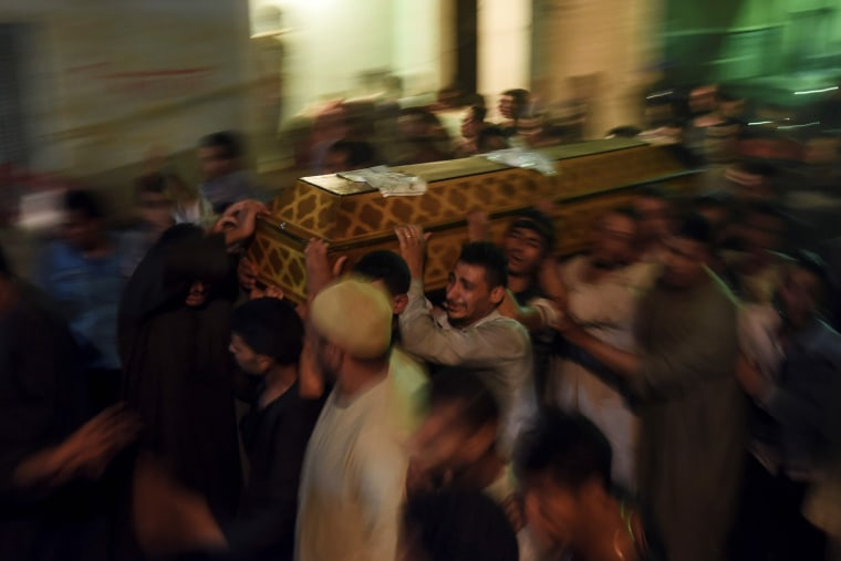Image: Relatives of killed Coptic Christians carry a coffin as they gather outside the Abu Garnous Cathedral