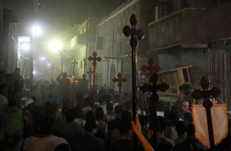 Image: Mourners carry crosses and march after the funeral of Coptic Christians who were killed on Friday in Minya