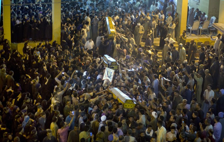 Image: Relatives of Coptic Christians carry coffins of their relatives who were killed during a bus attack, following their funeral service