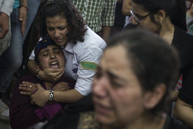 Image: Relatives mourn during the funeral of victims killed in an attack at the Monastery of St. Samuel the Confessor