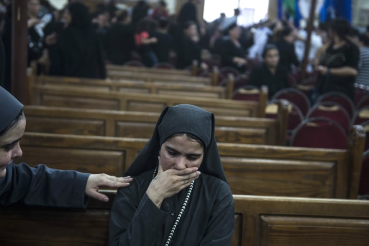 Image:  A woman is comforted as she mourns during the funeral of victims killed in an attack at the Monastery of St Samuel the Confessor,