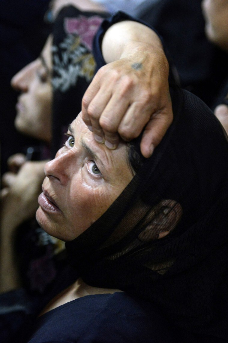 Image: A relative of killed Coptic Christians looks on during the funeral at Abu Garnous Cathedral