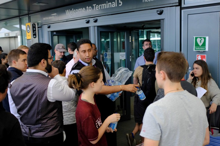 Image: An employee distributes water to stranded travelers outside the entrances of Heathrow Airport Terminal 5 after British Airways flights where canceled at Heathrow Airport in west London on May 27, 2017.
