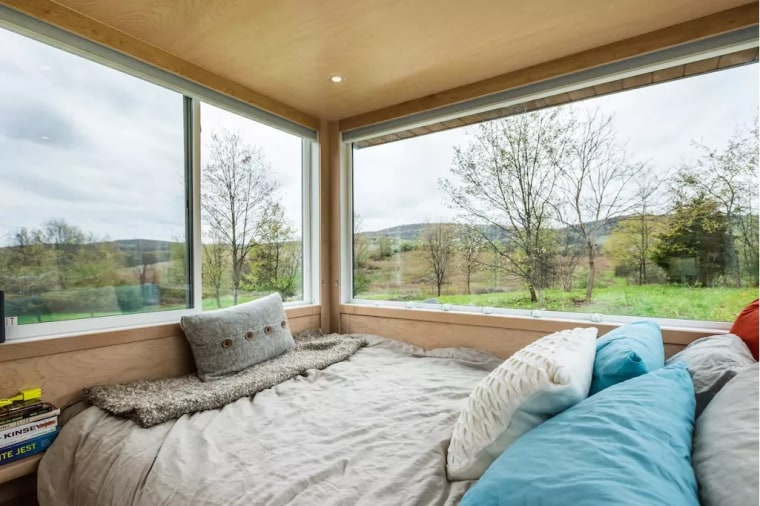 The queen-size bed has panoramic views of rolling hills on a farm in Marlboro, NY.