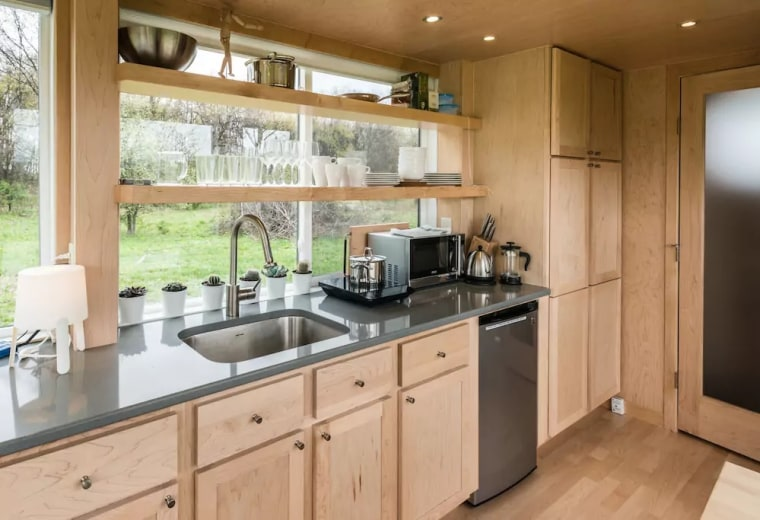 The stainless steel kitchen includes an induction cooktop, mini-fridge, a sink, microwave, electric kettle, French press and plenty of dishware.