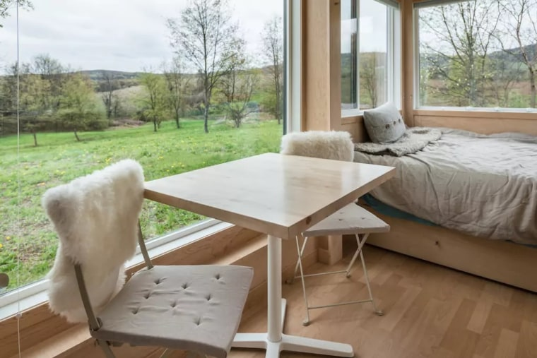 A simple table for two doubles as a work space in this glass-paneled tiny home in the Hudson Valley.