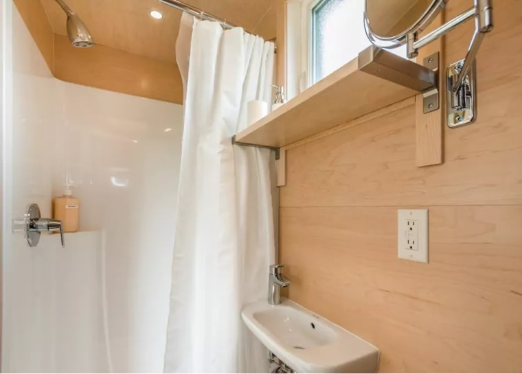 The bathroom has a standing shower, sink and sustainable dry-flush toilet.