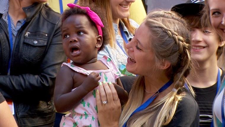 Lauren Rhett holds Willa as the little girl listens to dad perform.