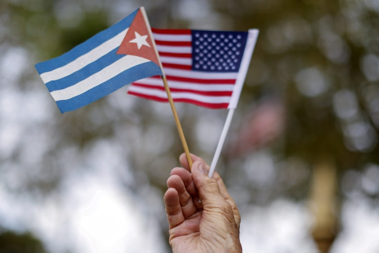 Image: A man holds Cuban and U.S flags in the Little Havana neighborhood of Miami, Florida on March 20, 2016.