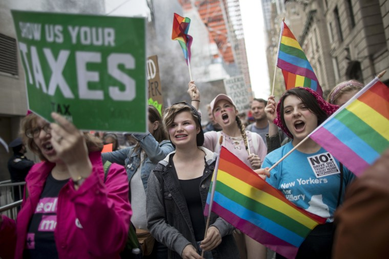 Image: Demonstrators carrying rainbow flags during he Tax Day rally