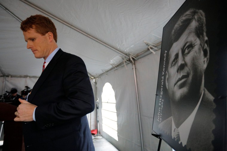 Image: U.S. Congressman Joe Kennedy III stands next to a poster of a stamp of featuring his great-uncle, U.S. President John F. Kennedy, in Brookline