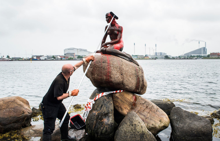 Image: A man cleans the Little Mermaid statue which was painted red in Copenhagen