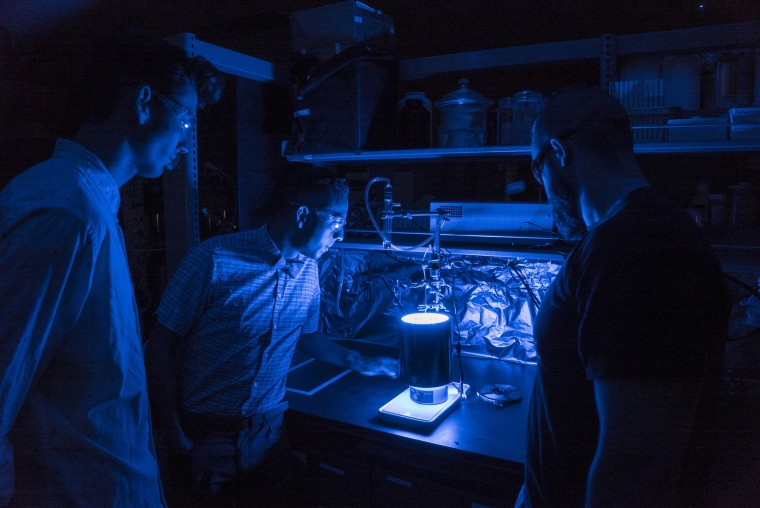 University of Central Florida Assistant Professor Fernando Uribe-Romo, center, has found a way to trigger the process of photosynthesis in a synthetic material.