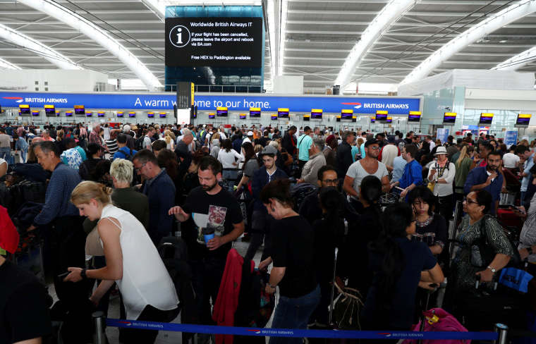 Image: People wait with their luggage at the British Airways check in desks at Heathrow Terminal 5 in London