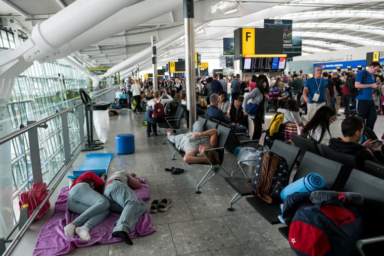 Image: People sleep on a blanket at Heathrow Airport Terminal 5