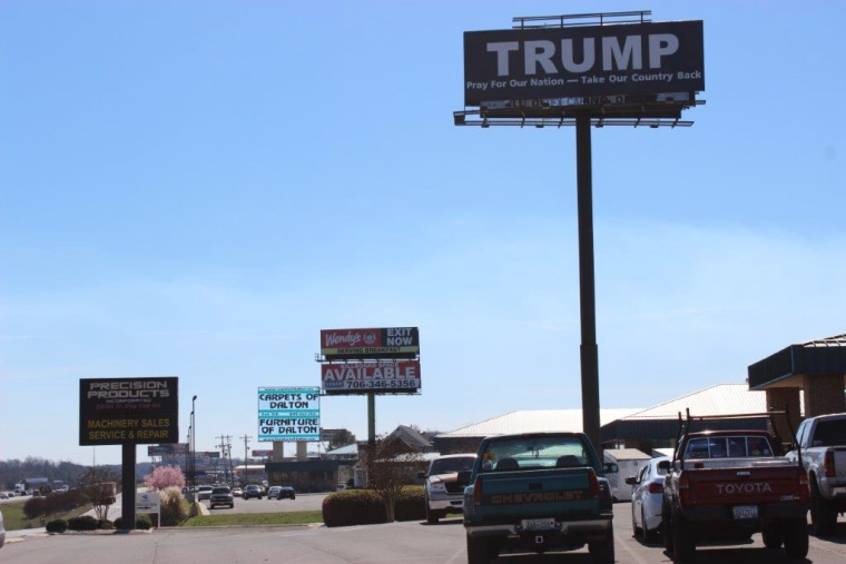 Image: A pro-Trump sign stands above others near carpet and flooring outlets and factories in Whitfield County