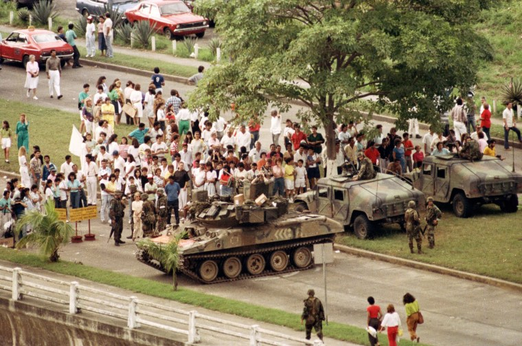 Image: U.S. Army armored vehicles form a blockade on Panama City's Balboa Avenue, leading towards the Vatican Embassy where Manuel Noriega has sought refuge