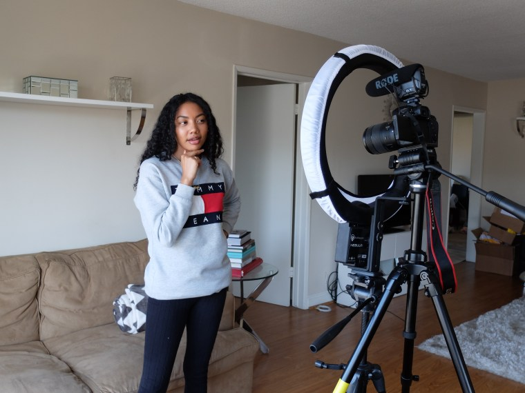 Filipino-American and black actress, model, and content creator Asia Jackson shooting a YouTube video.