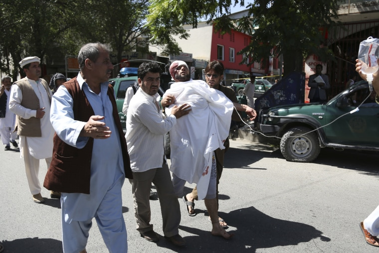 Image: People carry an injured man after a suicide attack in Kabul