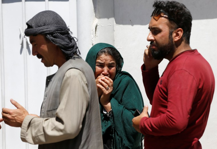 Image: Relatives of Afghan victims mourn outside a hospital after a blast in Kabul, Afghanistan
