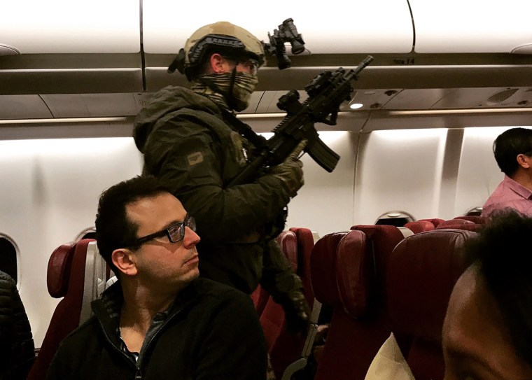 Image: An armed tactical officer sweeps a Malaysia Airlines flight at Melbourne Airport in Australia on Wednesday