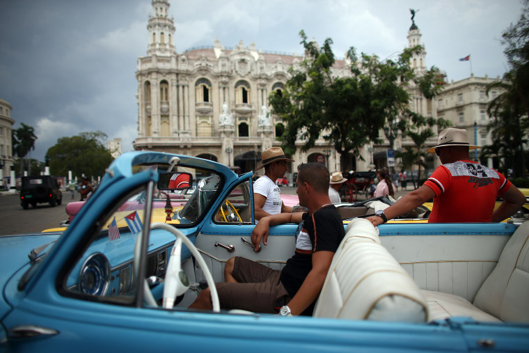 Image: Taxi drivers chat around their vintage American cars in Havana