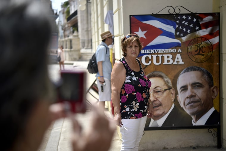 Image: A Cuban woman poses for a picture with a sign of Castro and Obama