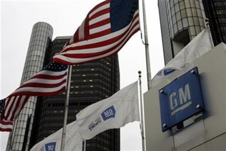 U.S. flags flutter in the wind in front of the General Motors Corp headquarters in Detroit