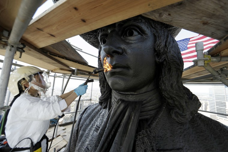 Image: Eliot Bassett-Cann, with Moorland Studios Inc., applies a protective coating to the sculpture of William Penn