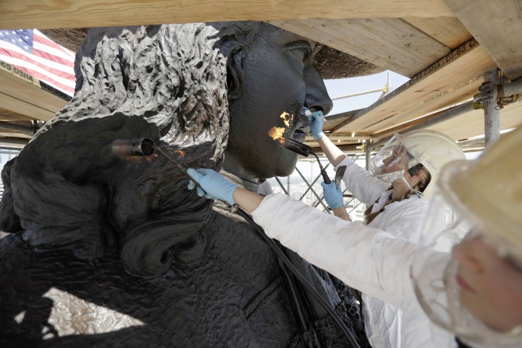 Image: Eliot Bassett-Cann, left, and Margaret Parrish, with Moorland Studios Inc., apply a protective coating to the sculpture of William Penn