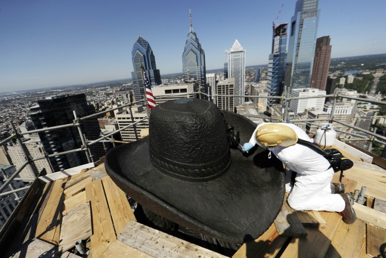 Image: James Bassett-Cann, with Moorland Studios Inc., applies a protective coating to the sculpture of William Penn atop City Hall