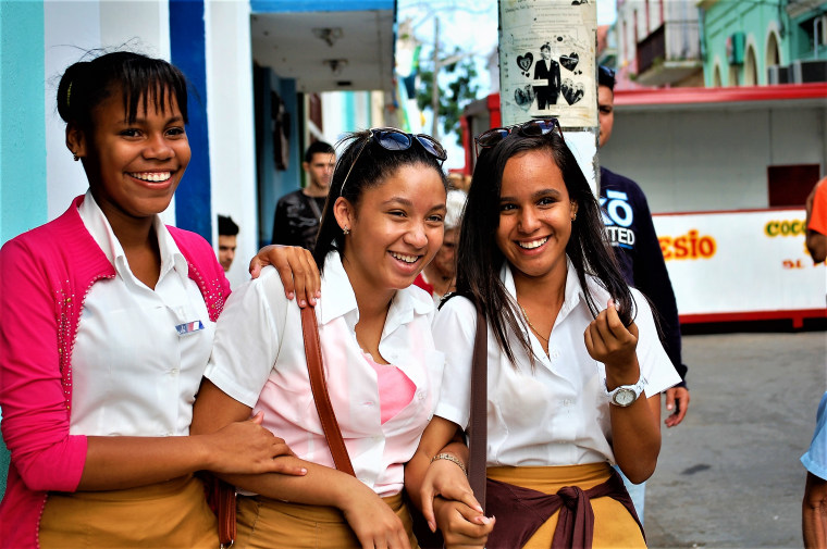 Image: three young girls pose in Central Havana